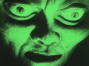 green face of a man with ghostlike features